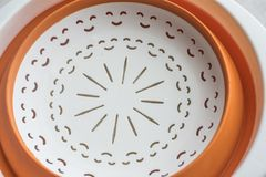 Bacia de fruto plástica branca com anel interno alaranjado embutido no fundo branco, vista inferior fotografia de stock royalty free