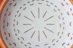 Bacia de fruto plástica branca com anel interno alaranjado embutido no fundo branco, vista inferior imagem de stock royalty free