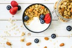 Bacia de granola com iogurte, bagas frescas, morango na madeira t Imagem de Stock Royalty Free