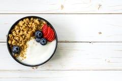 Bacia de granola com iogurte, bagas frescas, morango na madeira t Foto de Stock
