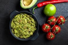 Bacia de guacamole com ingredientes frescos imagem de stock
