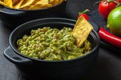 Bacia de guacamole com microplaquetas de milho imagens de stock royalty free