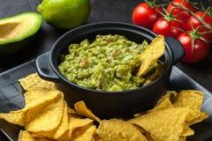 Bacia de guacamole com microplaquetas de milho imagem de stock