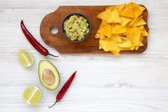 Bacia de guacamole e de ingredientes com nachos na placa de madeira W foto de stock royalty free