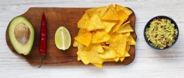 Bacia de guacamole e de ingredientes mexicanos tradicionais com nachos na placa de madeira em um fundo de madeira branco, em cima fotografia de stock royalty free
