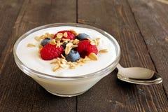 Bacia de iogurte com framboesas, mirtilos na madeira escura Fotos de Stock