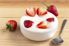 Bacia de iogurte e morango vermelha do fruto na tabela de madeira Iogurte feito do leite fermentado pelas bactérias adicionadas,  fotos de stock royalty free