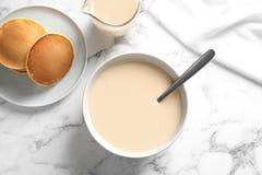 Bacia de leite condensado e de panquecas servidos na tabela de m?rmore Produtos l?cteos fotos de stock royalty free