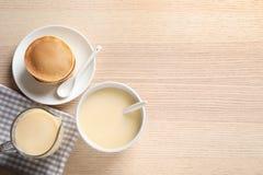 Bacia de leite condensado e de panquecas servidos na tabela de madeira, vista superior com espa?o para o texto imagens de stock