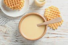 Bacia de leite condensado e de waffles servidos na tabela de madeira, vista superior imagens de stock royalty free