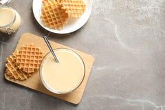 Bacia de leite condensado e de waffles servidos na tabela, vista superior com espa?o para o texto Produtos l?cteos fotos de stock royalty free