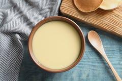 Bacia de leite condensado servido na tabela de madeira Produtos lácteos foto de stock royalty free