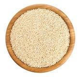 Bacia de madeira com as sementes de sésamo isoladas no fundo branco Fotografia de Stock