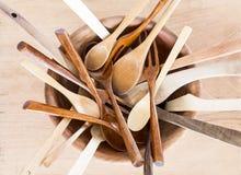 Bacia de madeira com colheres e forquilhas no fundo de madeira Imagem de Stock