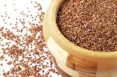 Bacia de madeira com os flaxseeds no fundo branco foto de stock
