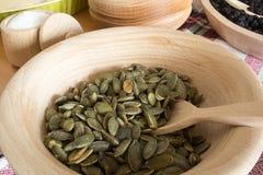 Bacia de madeira com sementes do pupkin fotos de stock