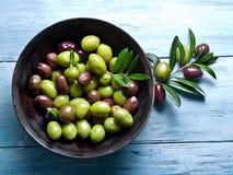Bacia de madeira completamente de azeitonas e de galhos verde-oliva foto de stock royalty free