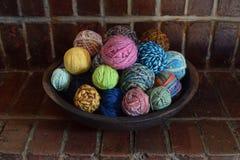 A bacia de madeira enchida com as bolas coloridas da mão girou o fio de lãs imagens de stock royalty free