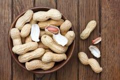 Bacia de madeira rústica de amendoins nos shell Fotos de Stock
