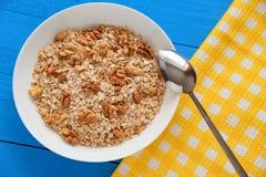 Bacia de nozes frescas da farinha de aveia no alimento rústico da tabela da cerceta, o quente e o saudável para o café da manhã Foto de Stock