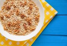 Bacia de nozes frescas da farinha de aveia no alimento rústico da tabela da cerceta, o quente e o saudável para o café da manhã Fotografia de Stock