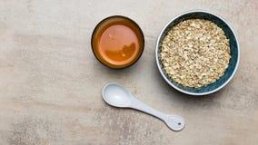 Bacia de papa de aveia da farinha de aveia com suco de cenoura imagem de stock royalty free