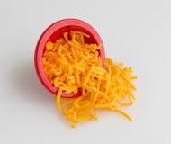 Bacia de queijo cheddar afiado shredded que derrama na placa de corte fotos de stock