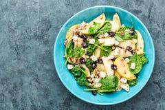 Bacia de salada de espinafres, do queijo do maçã, o branco, das porcas e do arando Imagens de Stock