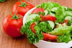 A bacia de salada misturada contra e de tomates é tabela de madeira Foto de Stock Royalty Free