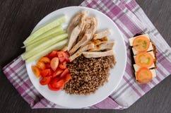 Bacia de salada saudável com tomates, galinha no fundo de madeira Fotos de Stock