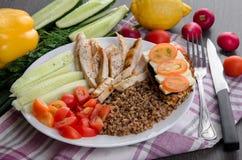 Bacia de salada saudável com tomates, galinha no fundo de madeira Imagem de Stock