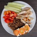 Bacia de salada saudável com tomates, galinha no fundo de madeira Foto de Stock