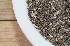 Bacia de sementes do chia no fundo de madeira foto de stock royalty free