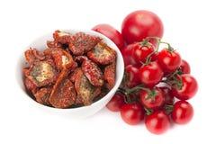 A bacia de sol secou tomates e montão de tomates frescos maduros Imagem de Stock
