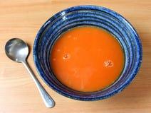 Bacia de sopa azul com sopa vermelha do tomate e uma colher Foto de Stock