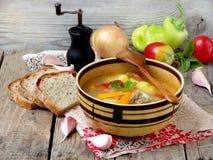 Bacia de sopa com batatas, cenouras, pimentas doces e tomates em um fundo de madeira Foto de Stock