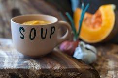 Bacia de sopa da abóbora na superfície de madeira com fundo do borrão da cebola e da abóbora Fotografia de Stock Royalty Free
