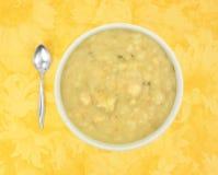 Bacia de sopa da batata e do alho-porro com uma colher Foto de Stock