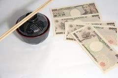 Bacia de sopa vermelha do Miso da borda da cor preta e hashis de madeira com as cédulas dos ienes de Japão no fundo branco imagem de stock