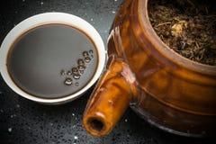Bacia de tisana chinesa e de um potenciômetro do esmalte com ervas imagens de stock royalty free