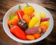 Bacia de vegetais orgânicos coloridos saudáveis frescos lavados e prontos para comer; pimentas doces e cenouras de bebê foto de stock