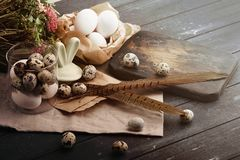 Bacia de vidro aberta com ovos de codorniz, orelhas do coelho, placa, penas e para chiken ovos Fundo de madeira tingido Ovos para fotografia de stock royalty free