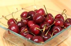 Bacia de vidro com as cerejas doces frescas fotografia de stock