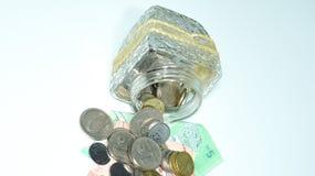Bacia de vidro com as pilhas das moedas e das cédulas de Malásia imagens de stock royalty free