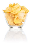 Bacia de vidro com de microplaquetas de batata da pilha no branco Imagens de Stock