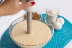 Bacia de vidro com massa e batedor de ovos em uma mão, grupo de produto Fotografia de Stock Royalty Free