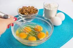 Bacia de vidro com ovos da galinha e mão fêmea com batedor de ovos, grupo de Fotos de Stock Royalty Free