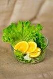 Bacia de vidro com salada verde fresca e as laranjas cortadas na lona Imagem de Stock