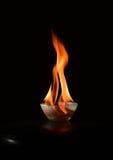 Bacia de vidro pequena com o ascendente próximo de ardência do fogo Fotos de Stock Royalty Free