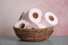 Bacia de vime com rolos do papel higiênico fotografia de stock